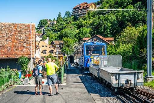 Cog railway train going to Rochers-de-Naye and two tourists hikers in Montreux old town Switzerland