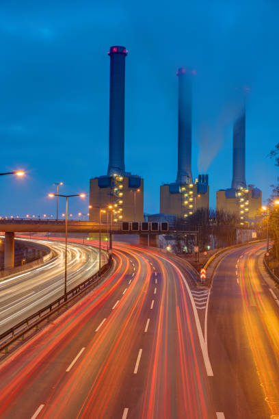 cogeneration plant and highway at night - cogeneration plant stock photos and pictures