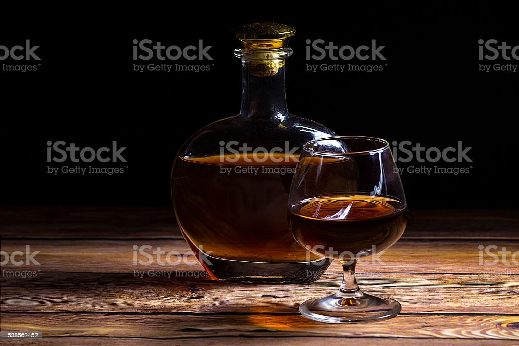 Cognac bottle and glass on the wooden table stock photo