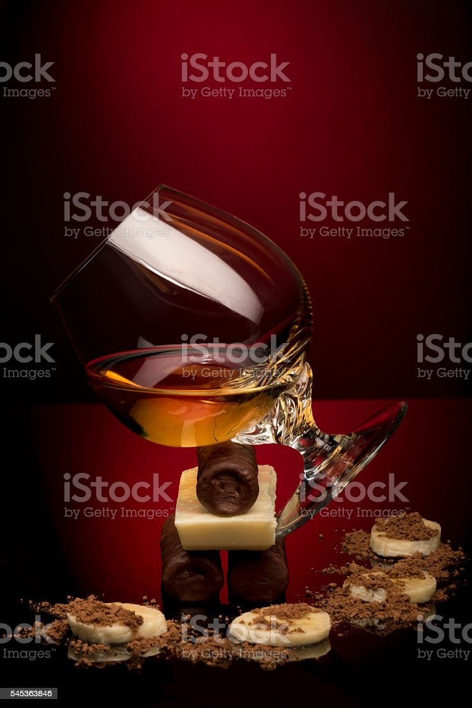 Cognac glass and  chocolate candies on red background stock photo
