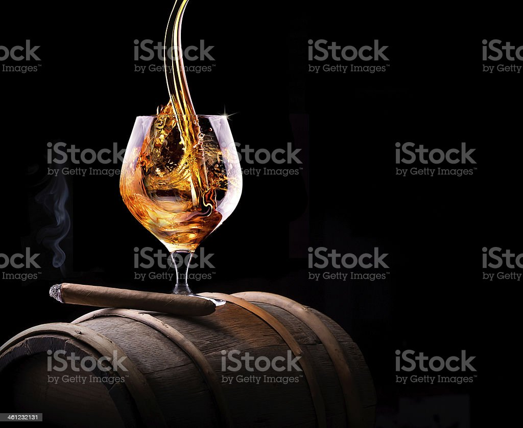 Cognac glass on barrel with lit cigar stock photo