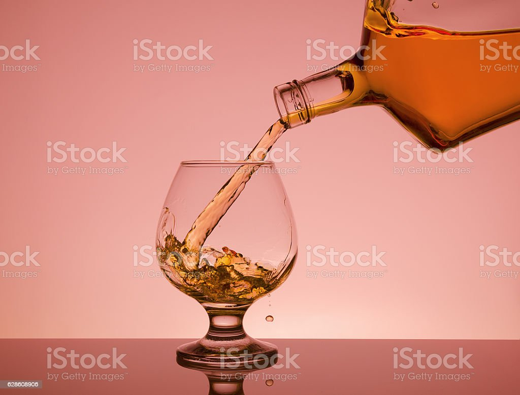 Cognac pouring from bottle into glass with splash stock photo