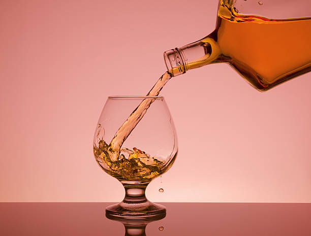 cognac pouring from bottle into glass with splash - orangenlikör stock-fotos und bilder