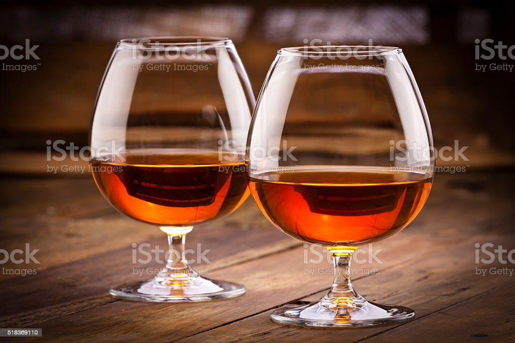 Cognac snifters on rustic wood table stock photo