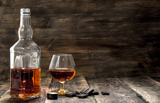 Cognac with bitter chocolate. Cognac with bitter chocolate. On a wooden background. brandy stock pictures, royalty-free photos & images