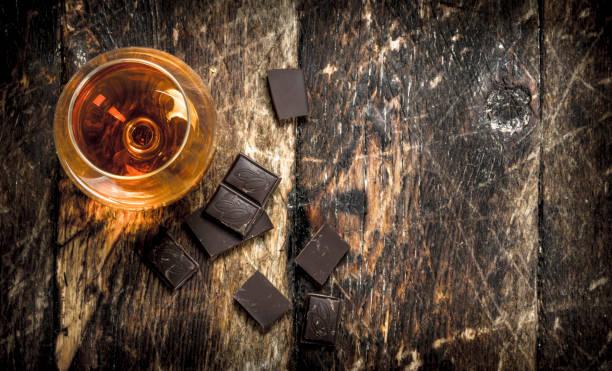 cognac mit bitterschokolade. - schokolikör stock-fotos und bilder