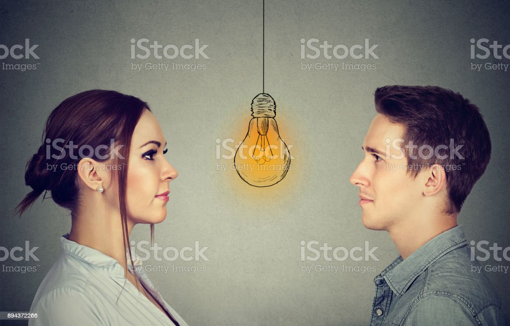 Cognitive skills ability concept, male vs female. Man and woman looking at bright light bulb isolated on gray wall background stock photo