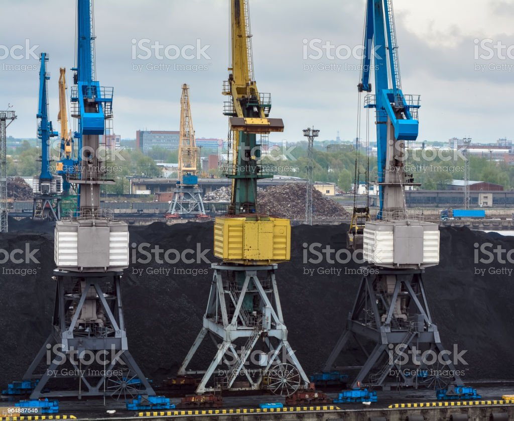 Coil transportation site including three colorful blue and yellow cranes royalty-free stock photo