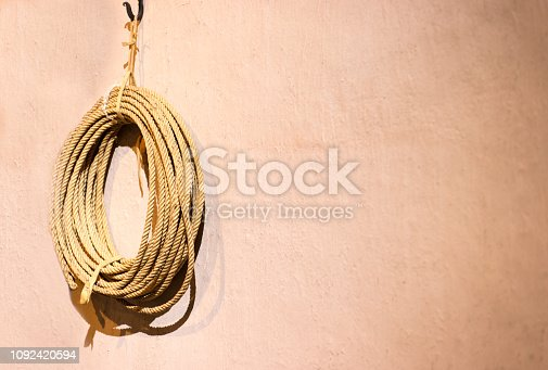 Strong coiled rope hanging on pinkish-orange wall, with plenty of copy space.
