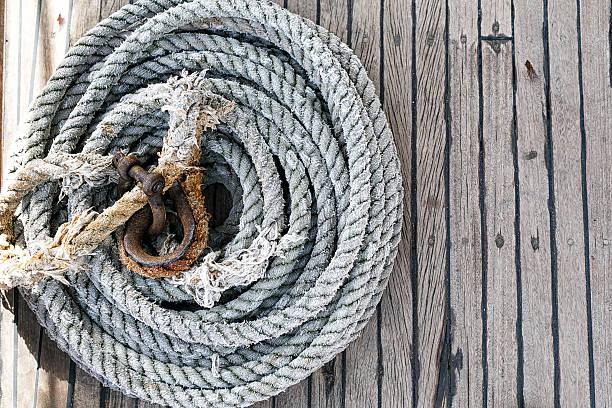 verschlungenes seil auf einem hölzernen deck - nautische seil stock-fotos und bilder
