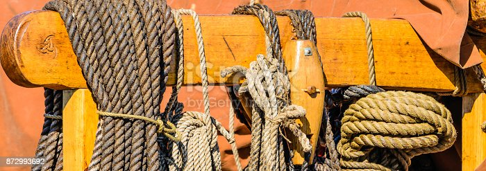 Coiled ropes on a post and beam of a ship replica.