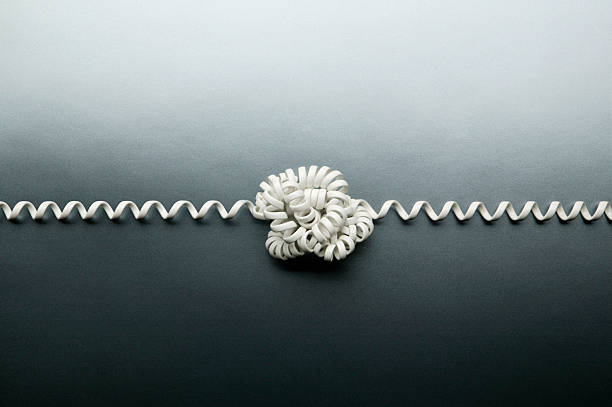 coiled telephone cord tied in a knot on gray background - tangled stock photos and pictures