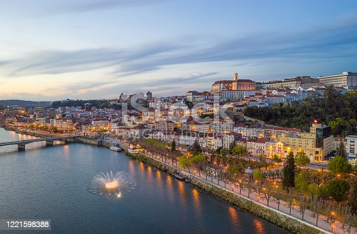 Coimbra drone aerial city view at sunset with colorful fountain in Mondego river and beautiful historic buildings, in Portugal