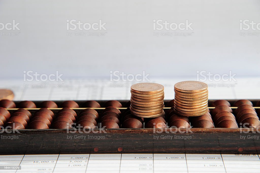 Coin and Abacus on Business Paper royalty-free stock photo