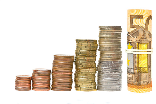 Coin columns and rolled banknotes isolated over white