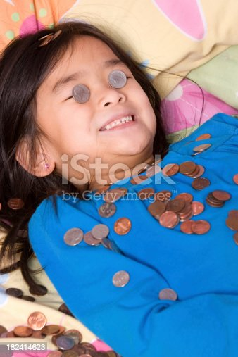 Little girl with nickels over eyes and coins surrounding her
