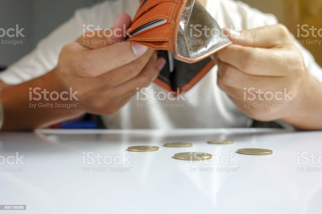 Coin falling from wallet - Little money concept stock photo