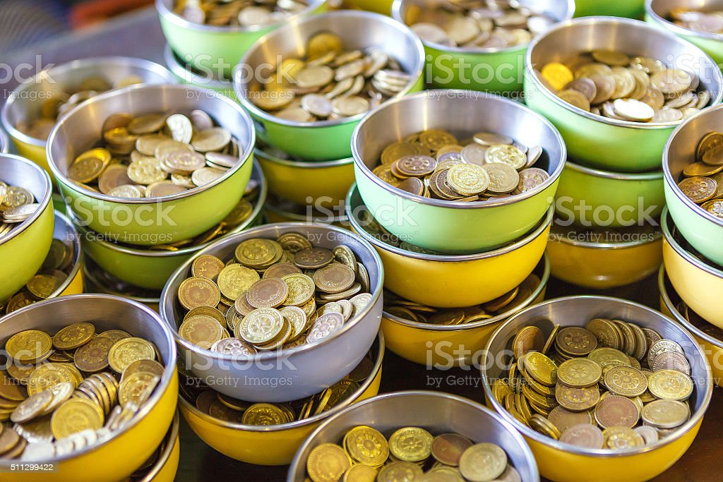 Coin in bowl for donation, temple of Thailand. stock photo