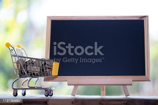 614338352istockphoto coin is in a small cart with blank chalkboard using as business and financial concept 1137956901