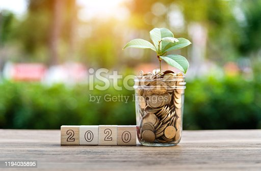 1170746979 istock photo Coin jar and number 2020 on the table 1194035895
