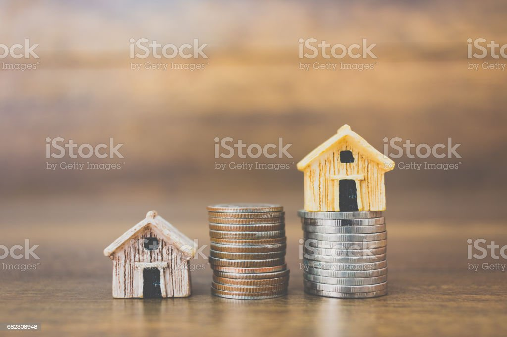 Coin money and house model on wooden background royalty-free stock photo