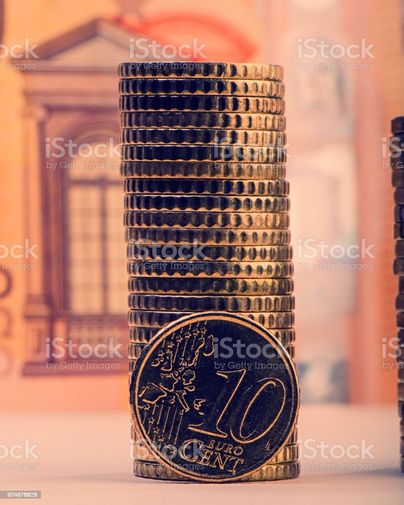 coin of ten euro cents on the background of folded coins and a paper bill of fifty euros. Euro money. stock photo