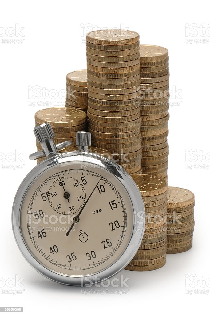 Coin pieces stacked up with an old pocket watch in front royalty-free stock photo