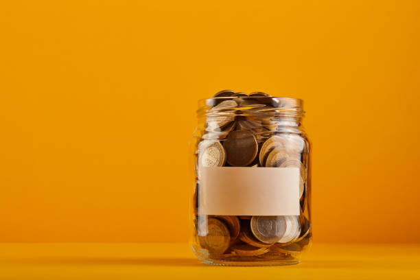 Coin savings jar with a blank label filled with cash over yellow / orange background stock photo
