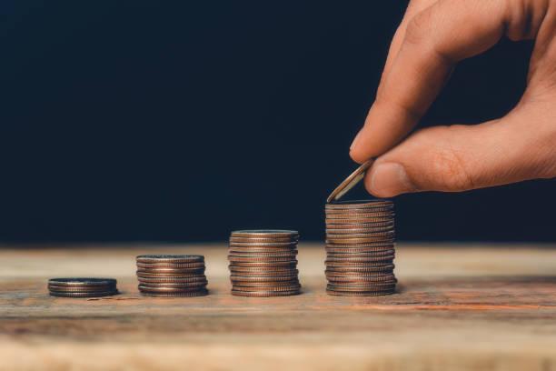 Münze stapelt Nahaufnahme mit Hand setzen ein US-Viertel auf dem höchsten Haufen. Finanz- und Unternehmenswachstum, Wirtschaft, Vermögen, Sparen oder Bankenkonzept. – Foto