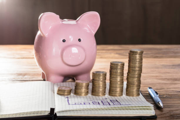 Coin Stacks With Graph On Notebook In Front Of Piggybank Pink Piggybank With Increasing Coin Stacks And Graph On Notebook Over The Wooden Table 40 kilometre stock pictures, royalty-free photos & images