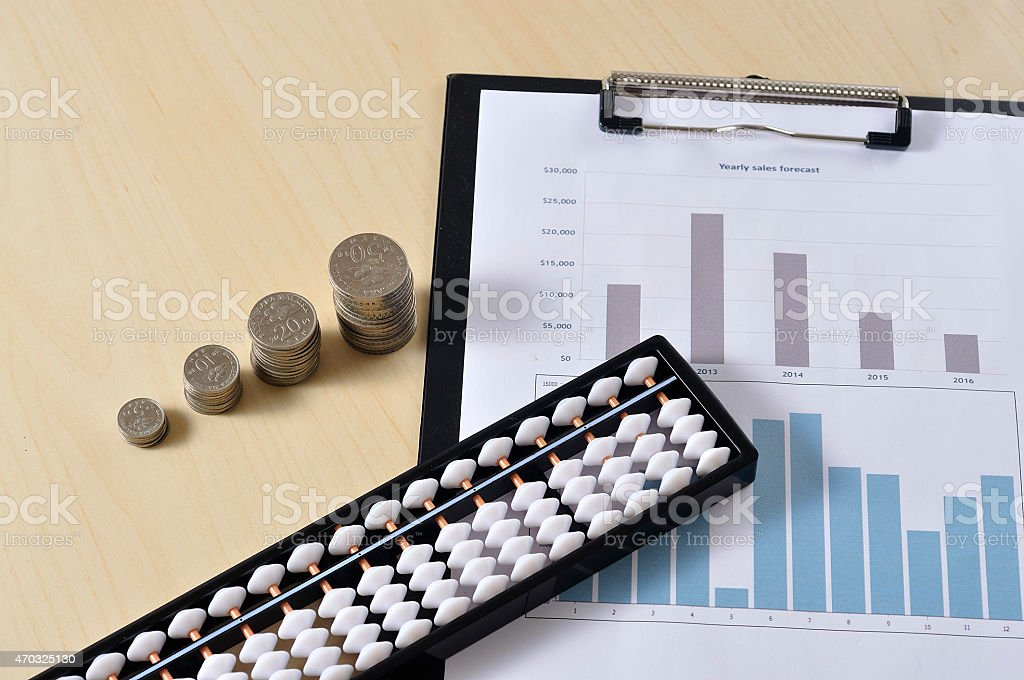 Coin With Abacus and Yearly Graph on Wooden Table stock photo