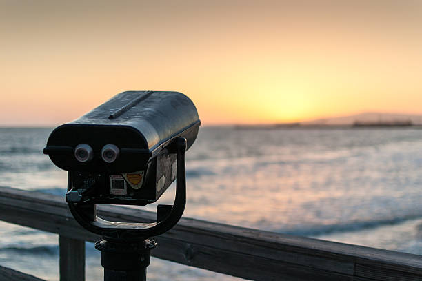 Coin-operated binoculars on pier at sunset overlooks ocean stock photo