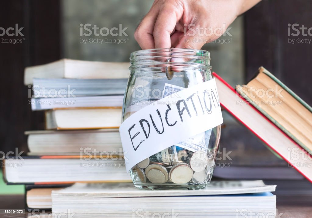Coins and banknote in a glass jar placed on the textbook. stock photo