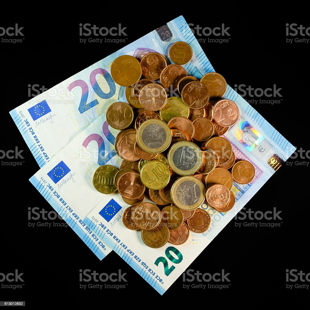 coins and banknotes on a black background stock photo