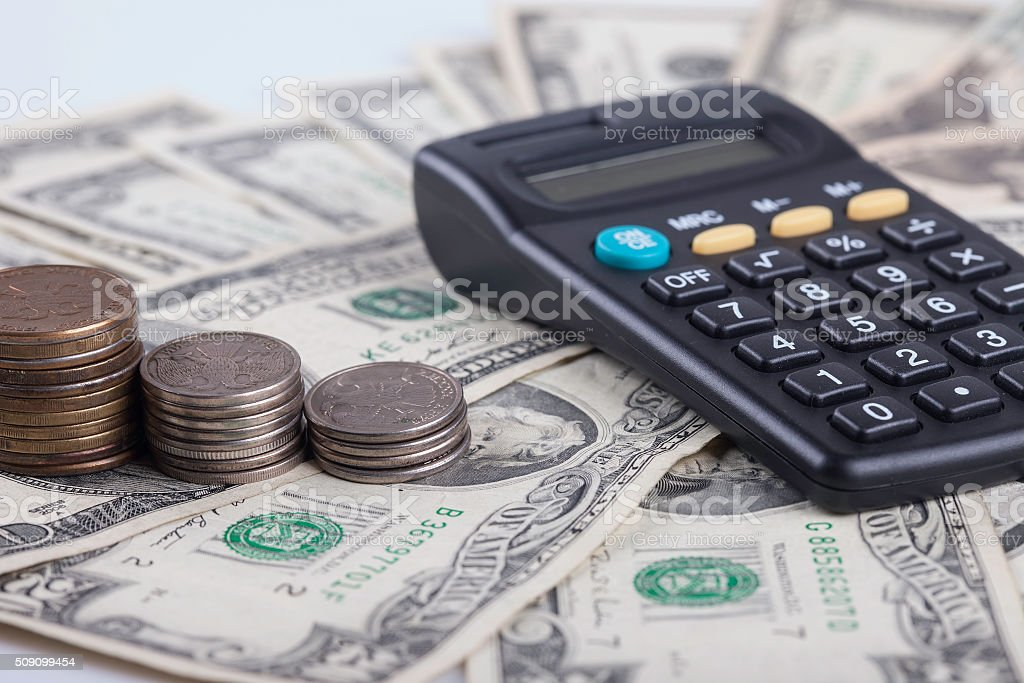 coins and calculator on the background of dollar banknotes stock photo