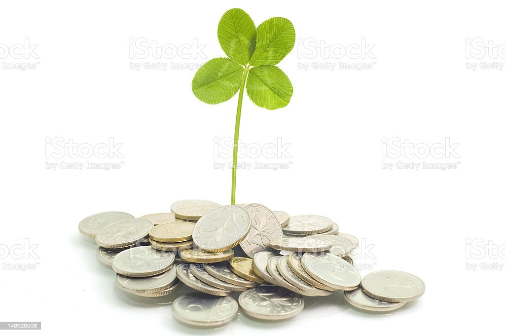 Coins and clover, isolated on white background royalty-free stock photo