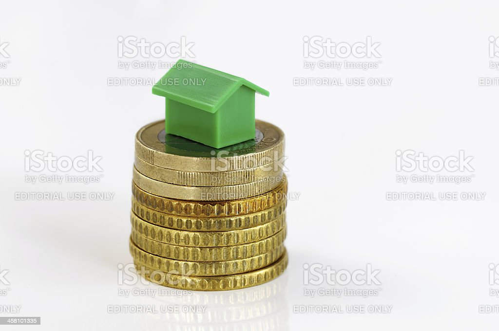 Coins and green model house stock photo