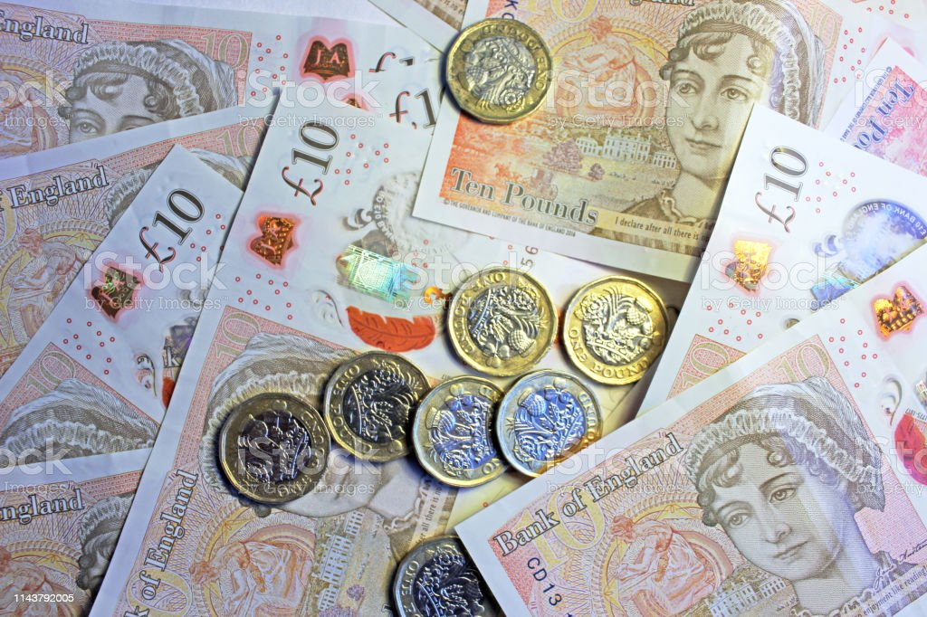 Coins & Banknotes Close-up of pound coins on ten pound notes. Backgrounds Stock Photo