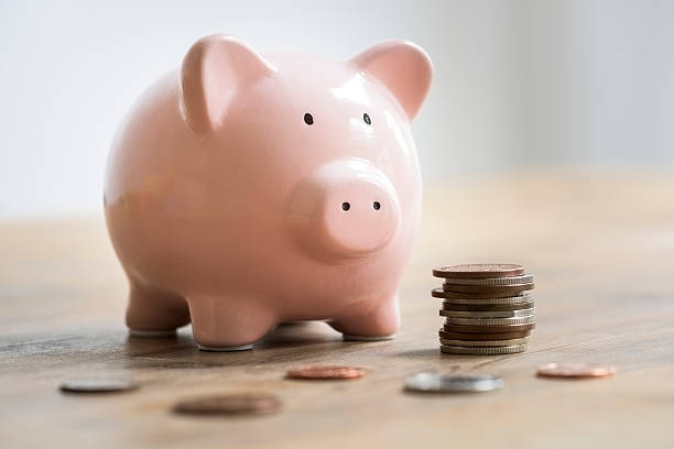 Coins beside a pink piggy bank to deposit and save stock photo
