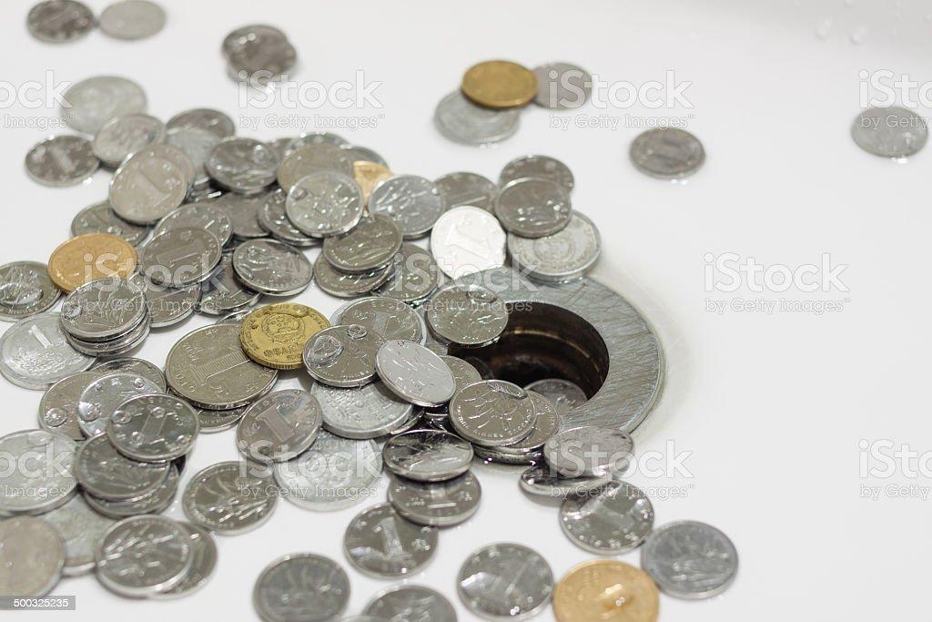 Coins down the drain stock photo