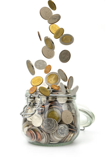 coins falling on pile of money into glass jar on white background .saving money for business and financial concept.save for retirement planning. - disbursement stock pictures, royalty-free photos & images