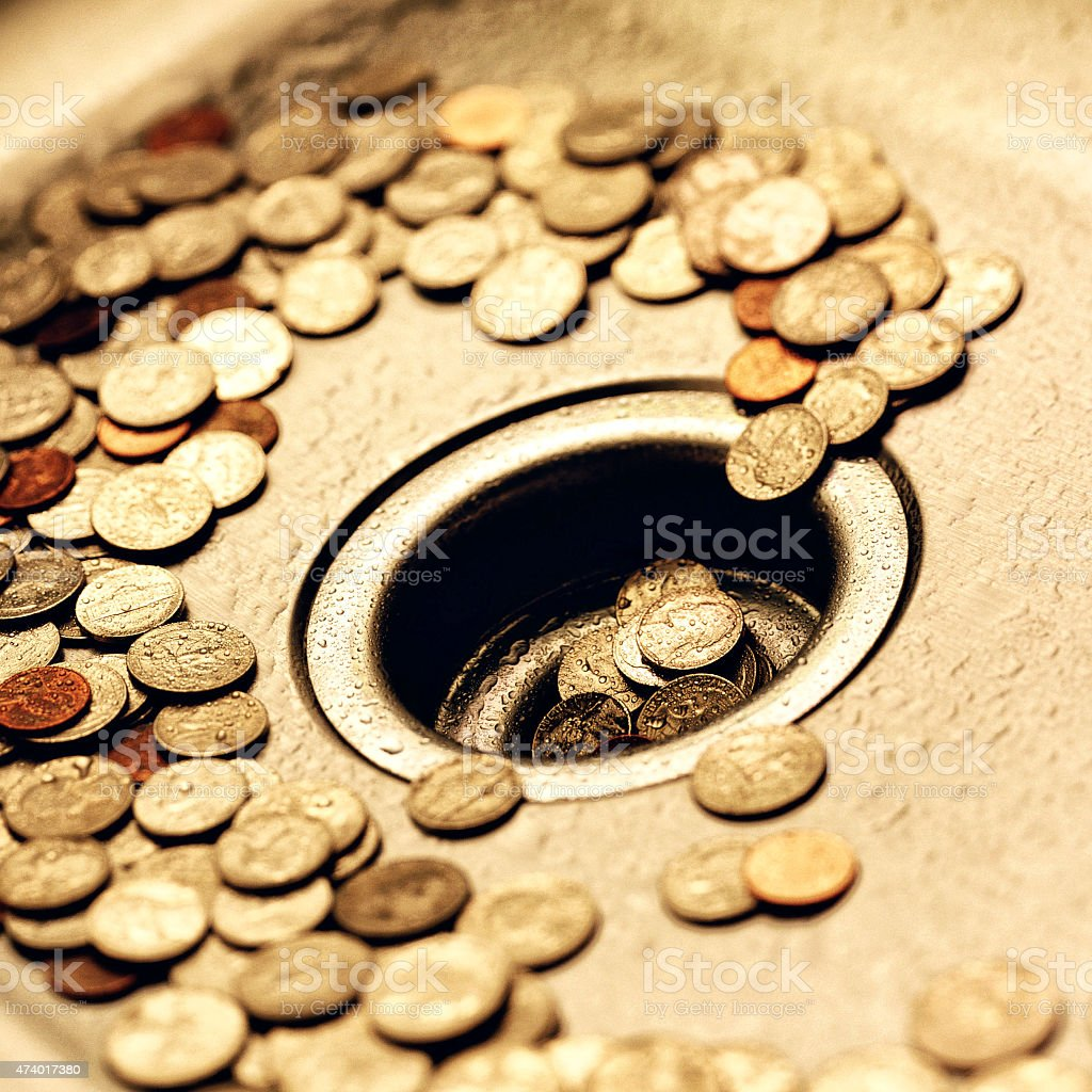 US coins going down a drain. stock photo