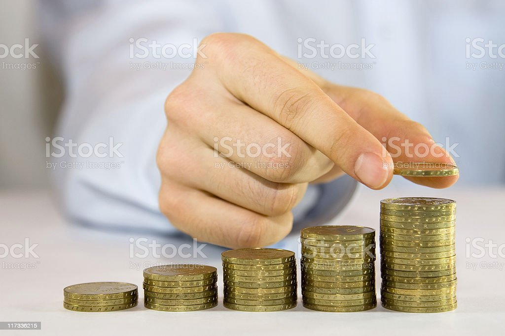 Coins gradually increasing in size being placed by a man royalty-free stock photo