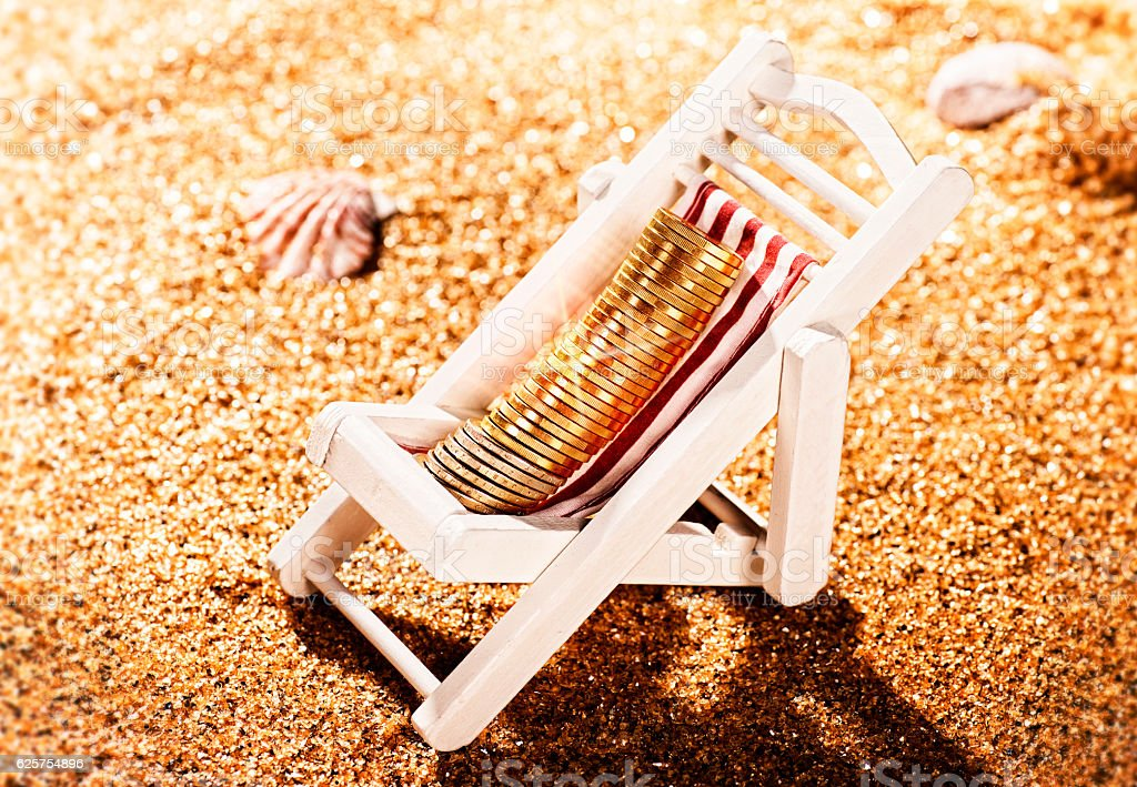 Coins in a deck chair on the beach stock photo