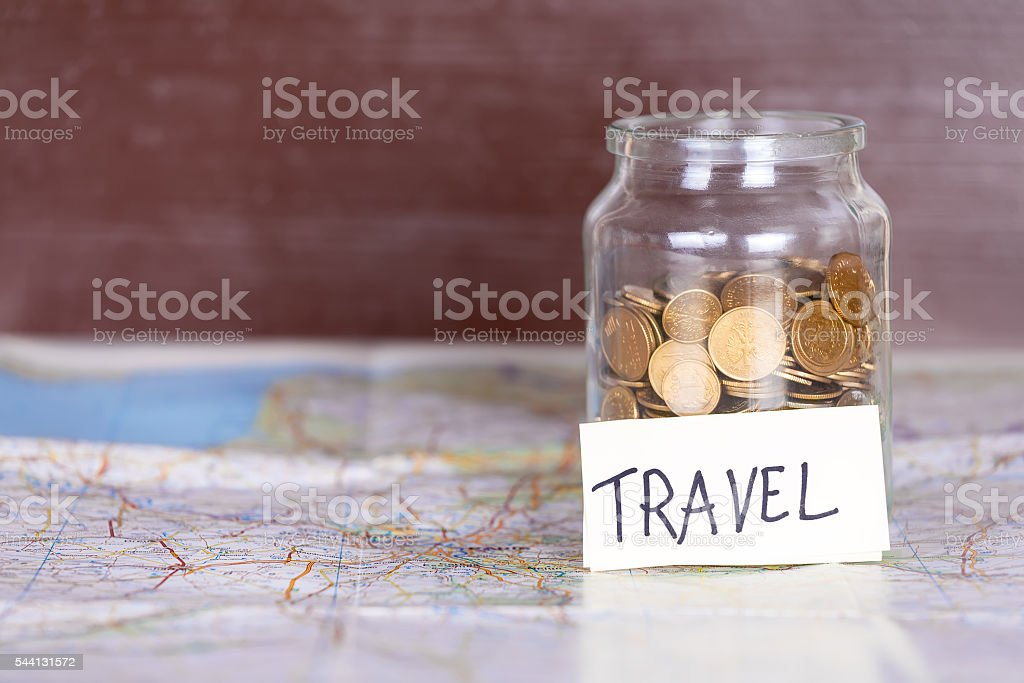 Coins in a jar with travel sign on a map. stock photo