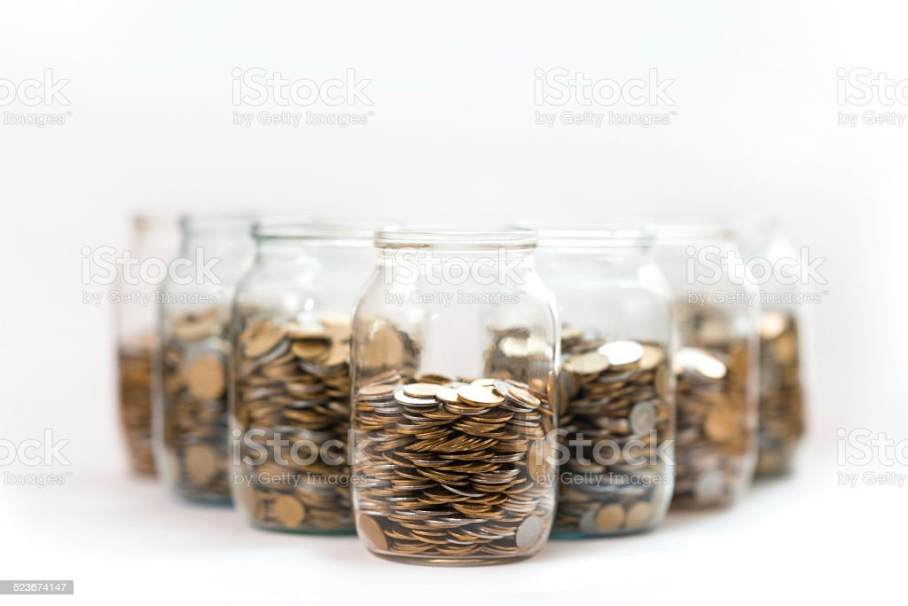 coins in a three glass jars against a white background stock photo