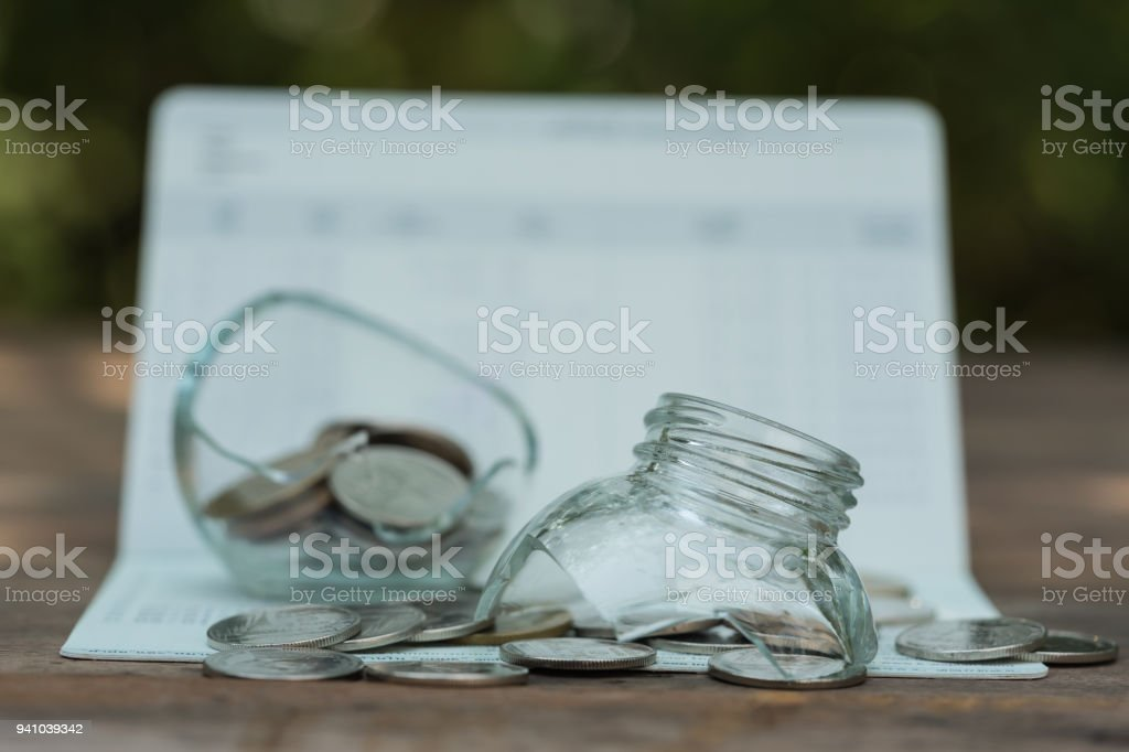 Coins in broken glass jar for money saving for housing,financial concept stock photo