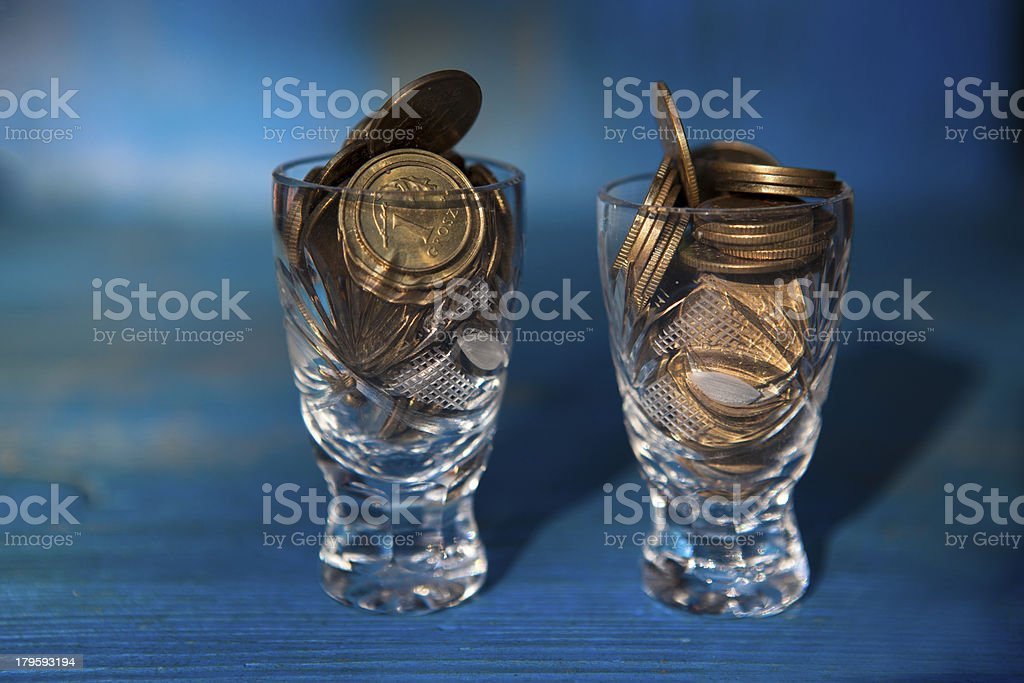 Coins in crystal glasses - symbol of alcoholism. royalty-free stock photo