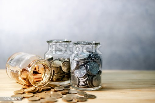 istock Coins in currency glass jars and spilling on wooden table. Saving money for future retirement. Financial business investment concept 1040759730