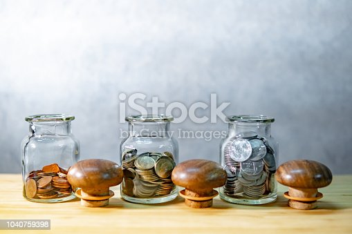 istock Coins in currency glass jars on wooden table. Saving money for future retirement. Financial business investment concept 1040759398